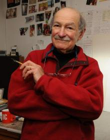 Ed Koren, in his studio, holding a pen
