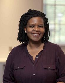 Annette Gordon-Reed is wearing a dark plum shirt, standing in front of a window